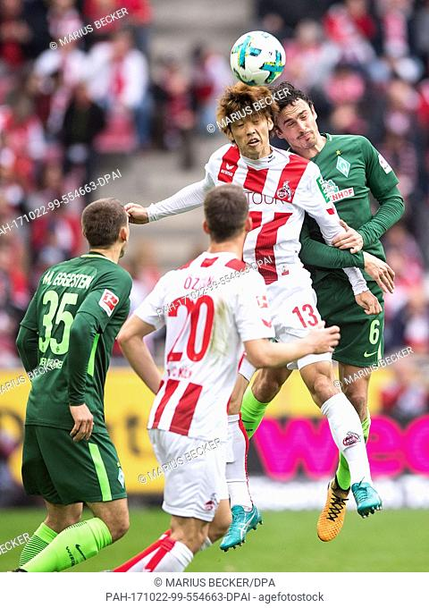 Cologne's Yuya Osako and Bremen's Thomas Delaney (r) vie for the ball during the German Bundesliga soccer match between 1