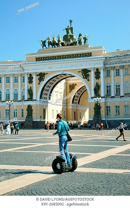 Saint Petersburg Russia. Tourist riding Segway across Palace Square in front of double arch of the General Staff Building