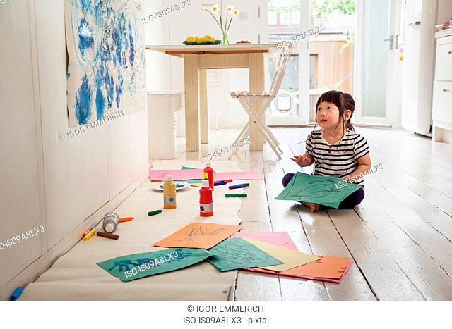 Female toddler sitting on floor with drawings