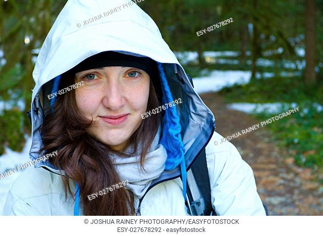 A woman pauses during her hike for a rest and to look at the camera while wearing a white jacket