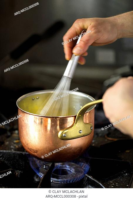 Close-up Of Chef Whisking Food In A Pot, Piedmont, Italy