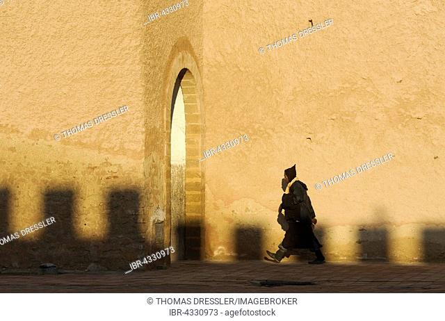 Man walking in front of the city wall of Essaouira, Morocco