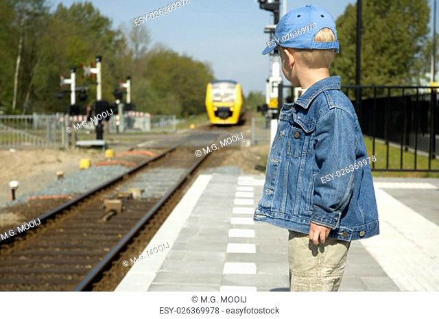 Little boy waiting for the train to come on a railway station