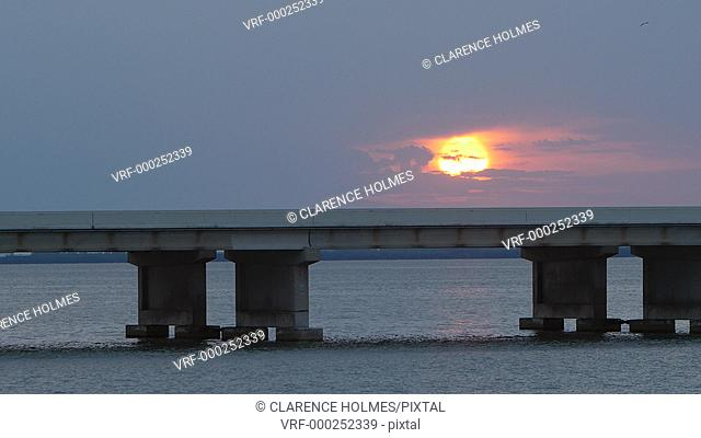 The sun rises over Tampa Bay as traffic crosses the Sunshine Skyway Bridge, as viewed from the south fishing pier