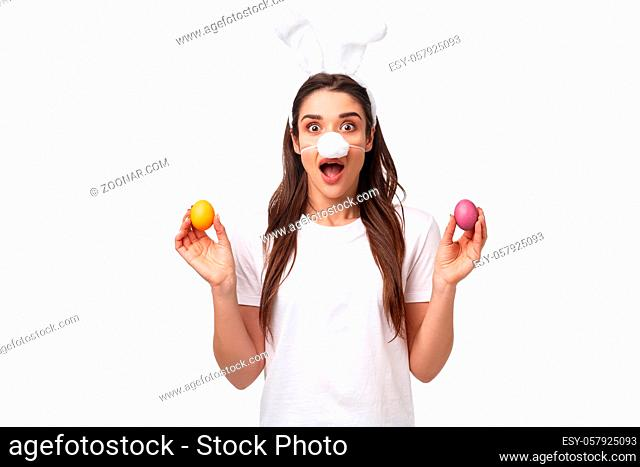 Easter party begins. Portrait of funny and cute, silly young caucasian woman celebrating divine day, wear rabbit ears and nose, holding colored eggs