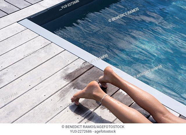 Girl's legs lying on decking by swimming pool