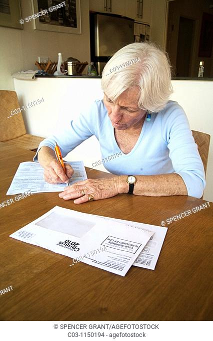 A woman fills out her 2010 U S  Census form at home in California  Administered every ten years, the census is an important tool of efficient government