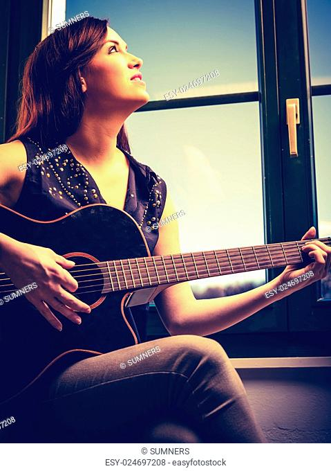Photo of a beautiful brunette female playing an acoustic guitar by the window. Heavily filtered