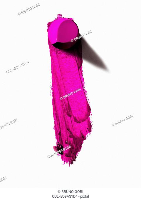Abstract of piece of pink lipstick and smudged line