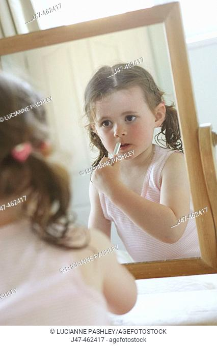 3 year old girl applying lipstck in a mirror