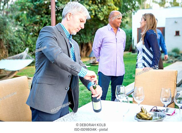 Mature man uncorking wine bottle at garden party table