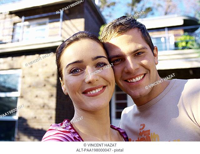 Man and woman standing cheek to cheek, smiling in front of a house