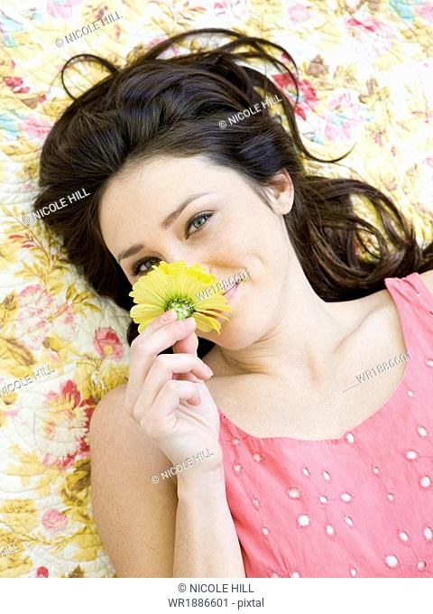 woman lying on a floral print blanket