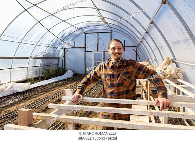 Caucasian farmer standing in greenhouse