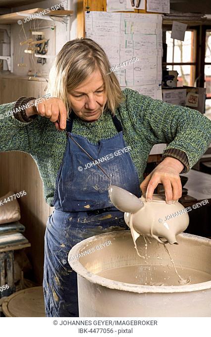 Ceramic workshop, woman douses pot with engobe, Pittenhart, Upper Bavaria, Germany