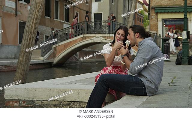 MS Couple eating ice cream,sitting on water's edge in old town / Venice,Veneto,Italy