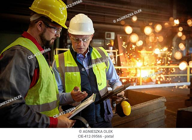Supervisor and steelworker with clipboard talking in steel mill