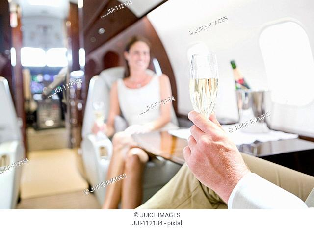 Close-up of glass of champagne in man's hand with woman in background on private jet