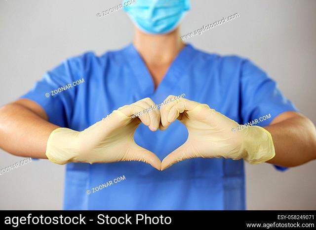 Female doctor in a face mask and gloves forming a heart in front of blue shirt with her fingers. Medical worker makes a positive symbol with fingers in latex...