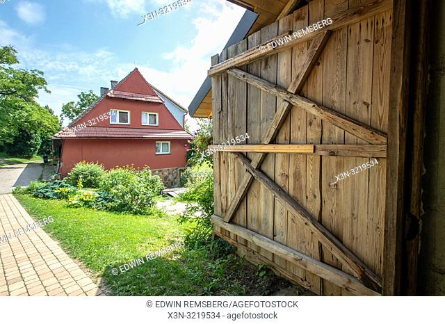 Wooden door and a small pathway leading to a red farm cottage with gardens. Glich—w, Lesser Poland Voivodeship, Poland