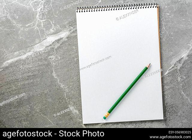 open notebook with green pencil on marble background top view, school notepad on a dark table, office desk flat lay