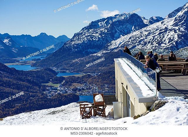 Tourists enjoy a sunny autumn day at the outdoor bar of Romantik Hotel Muottas Muragl overlooking Engadin Valley. Samedan. Majola District
