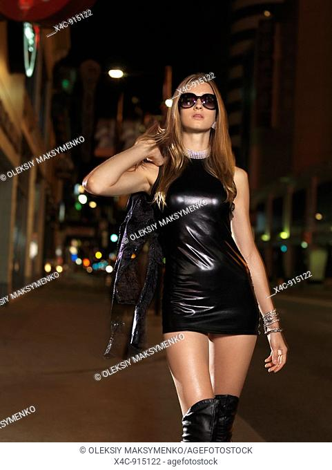 Attractive young woman in a sexy outfit walking down the street at night  Yonge Street, downtown Toronto, Ontario, Canada