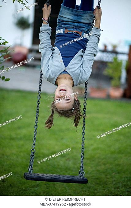 Girl hanging upside down on a swing in the garden