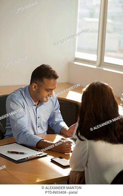 Singapore, Businessman and businesswoman looking at laptop on office