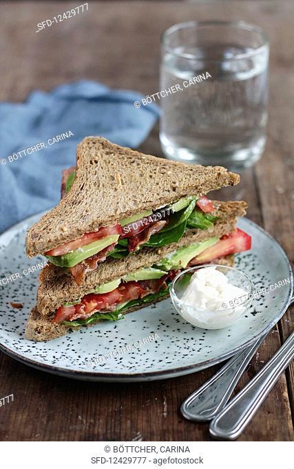 A BLT sandwich with avocado