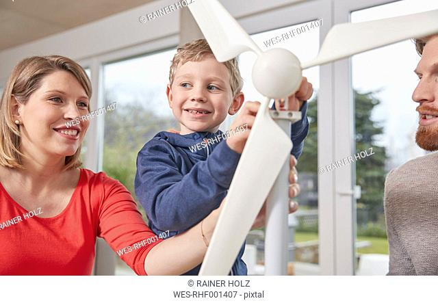 Family assembling toy wind turbine together