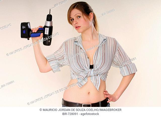 Young long-haired woman wearing crop top holding a drill