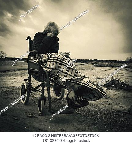 Old woman in wheelchair shielding herself from the wind