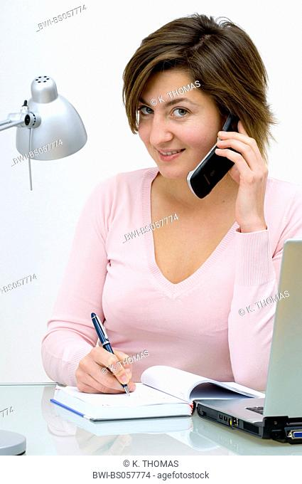 young woman sitting at the table with notebook, writing in her appointment calendar, talking on a mobile phone