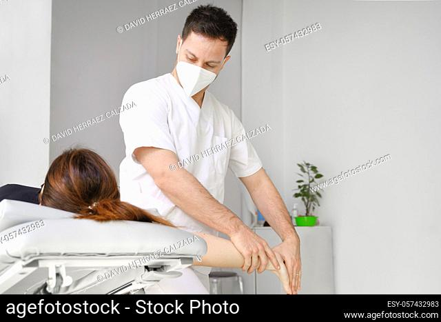 Male therapist giving massage to relief shoulder pain to a female patient in physiotheraphy clinic. High quality photo