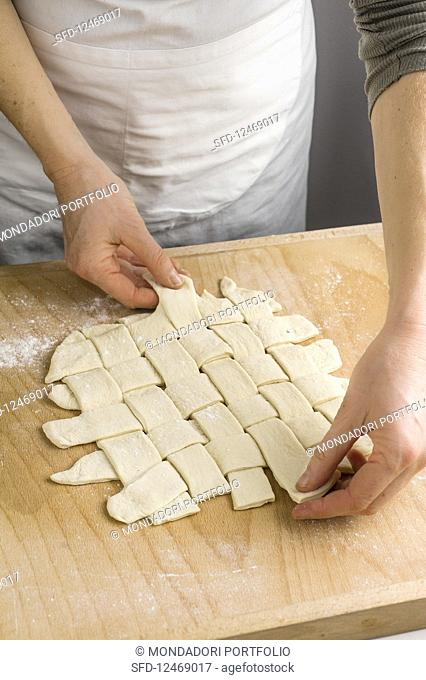 Dough strips being plaited for vegetable bread