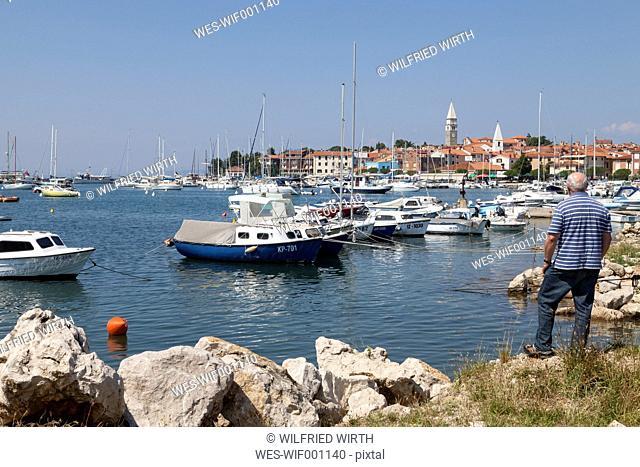 Slovenia, Istria, Izola, man at seashore with marina
