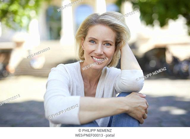 Portrait of smiling blond woman with hand in her hair