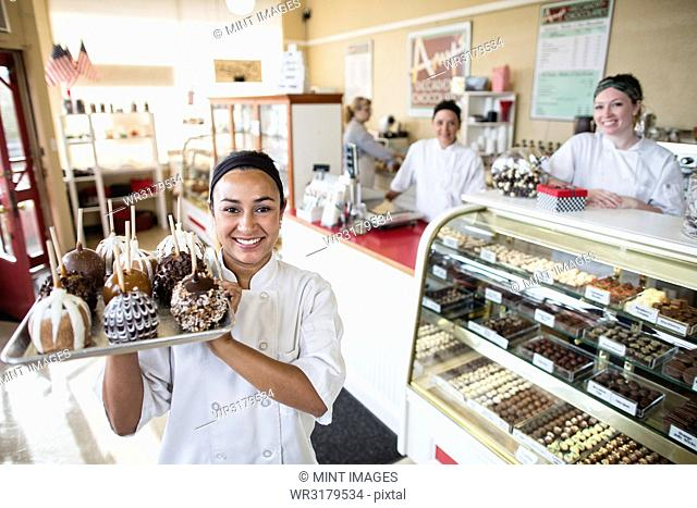 Hispanic woman owner of a candy shop and her staff in the background of the shop