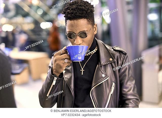 young fancy man sipping coffee from porcelain cup, African descent, in Munich, Germany