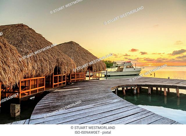 Waterfront chalets and moored motor boat, St. Georges Caye, Belize, Central America