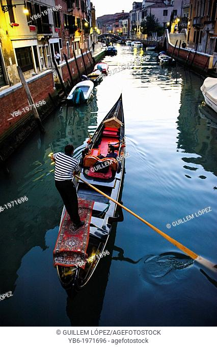 A couple in a gondola ride in a canal of Venice, Italy