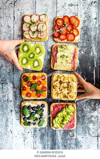 Children's hands taking garnished sandwiches