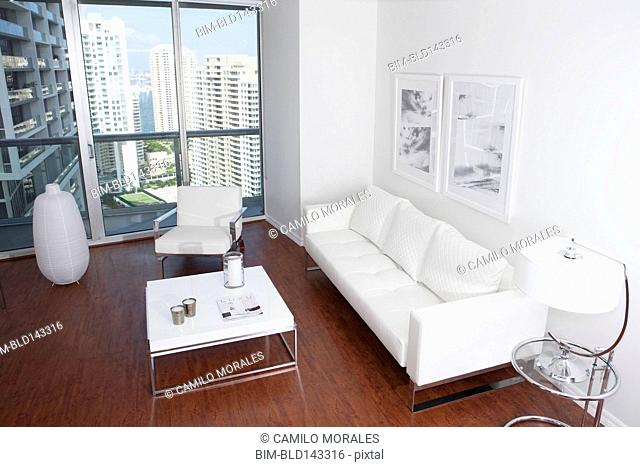 Sofa, coffee table and windows in modern apartment overlooking high rise buildings