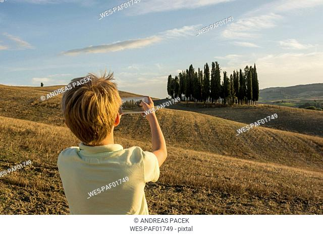 Italy, Tuscany, Boy taking pictures of landscape