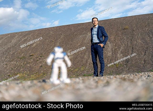 Businessman and miniature robot on a disused mine tip