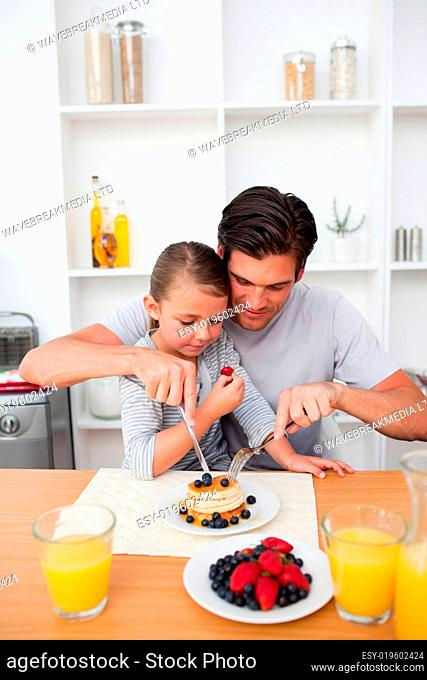 Portrait of a father eating pancakes with his daughter