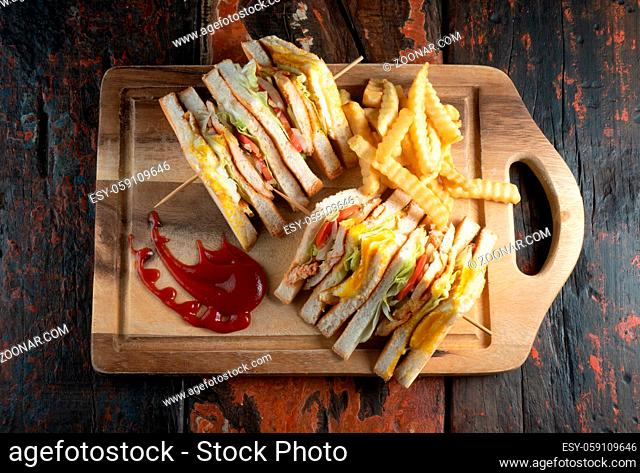 Top view of chicken club sandwiches and french fries isolated on rustic wooden table