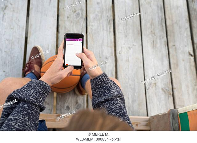 Teenage boy with basketball using smartphone