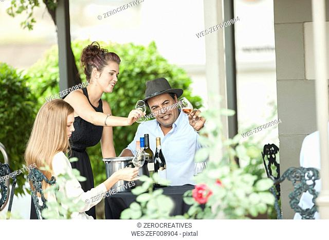 Waitress and clients in restaurant examining wine in glasses